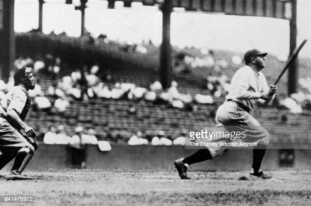 Babe Ruth watches his home run fly over the outfield wall in Dunn Field Cleveland Ohio August 20 1927 Luke Sewell is the Indians catcher