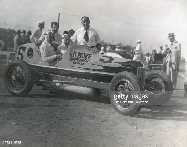 """Babe Stapp and a group of men pose with a race car that says """"Gilmore Speedway Special"""" on the side, circa 1935."""
