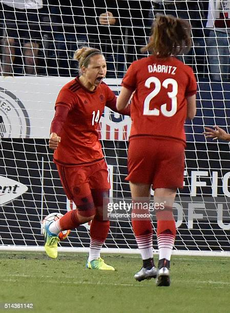 Babett Peter of Germany celebrates with teammate Sara Dabritz after scoring a goal against England in a friendly international match in the...