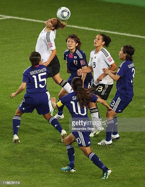 Babett Peter of Germany heads for the ball as her teammate Celia Okoyino Da Mbabi and Aya Sameshima Mizuho Sakaguchi Homare Sawa and Azusa Iwashimizu...