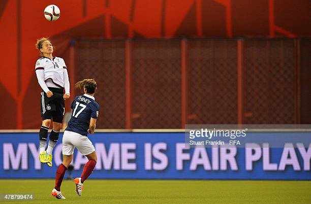 Babett Peter of Germany is challenged by Gaetane Thiney of France during the quarter final match of the FIFA Women's World Cup between Germany and...