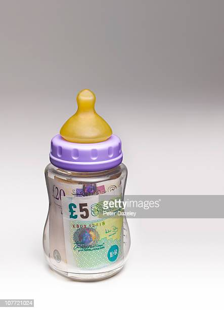 Babies feeding bottle with pound notes