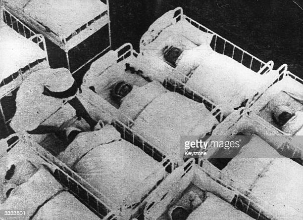 Babies in cots in a dormitory at a German unwed mothers home, where 'Aryan' youngsters, Hitler's perfect youth, were encouraged.