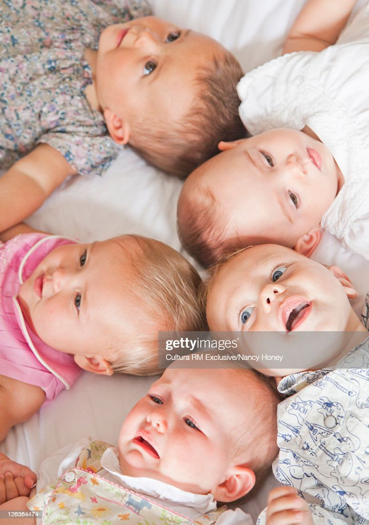 Babies laying on bed together : Bildbanksbilder