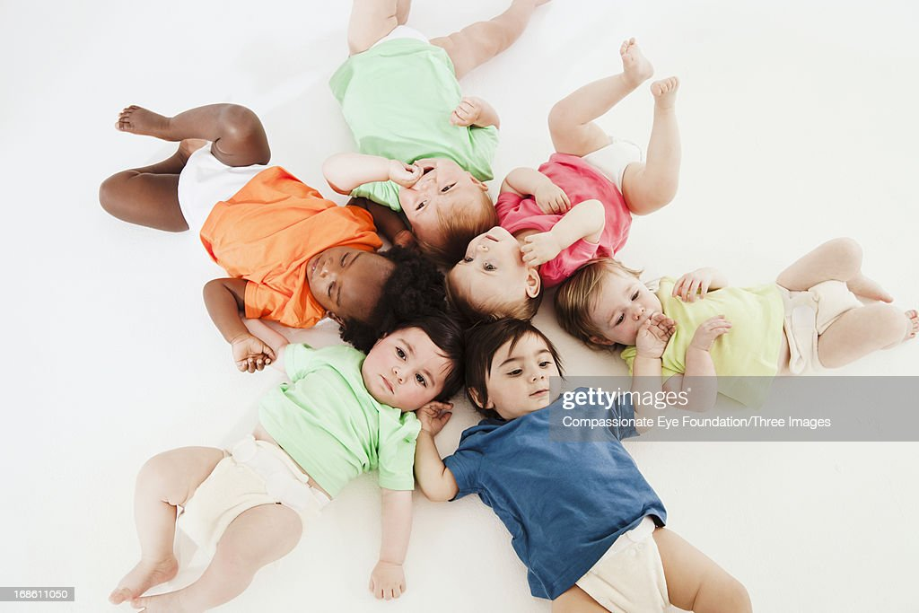 Babies laying on floor : Stock Photo
