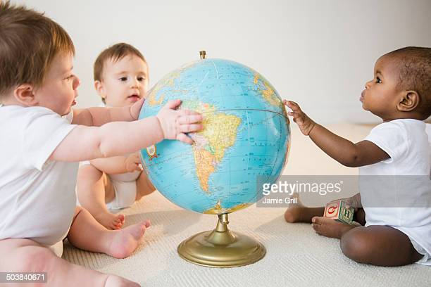 Babies looking at globe together