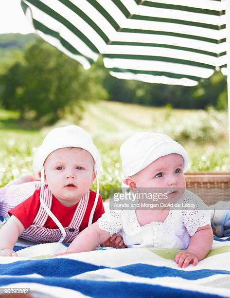 babies on blanket in field