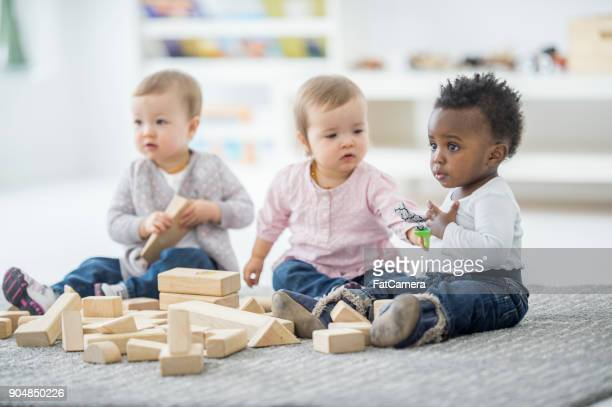 babies playing together - child care stock pictures, royalty-free photos & images