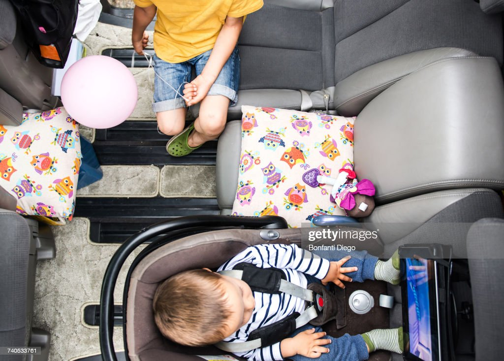 Baby and big brother watching movie in car : Stock Photo