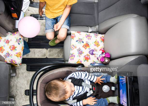 baby and big brother watching movie in car - family inside car stock photos and pictures