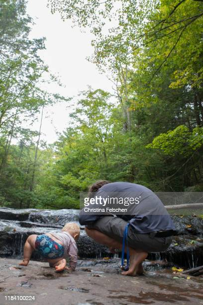 baby and father exploring a forest creek and waterfall together - christina felschen stock pictures, royalty-free photos & images