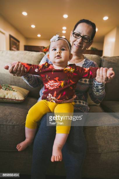 Baby and grandmother sitting on sofa