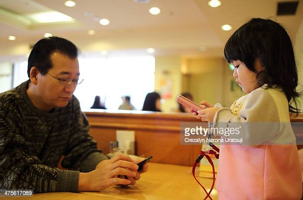 Baby and her dad busy with smartphones