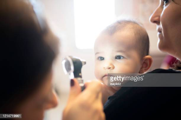 a baby and her doctor - eye test stock pictures, royalty-free photos & images