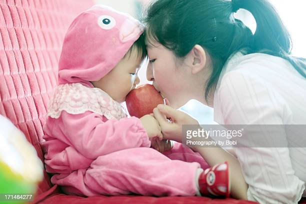 Baby and mather eating apple together