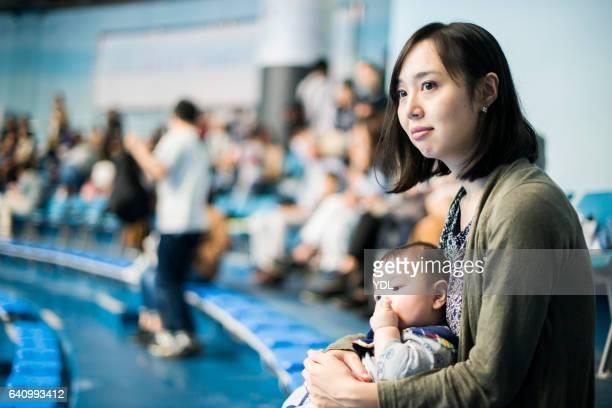 a baby and mother at stadium. - 注視する ストックフォトと画像