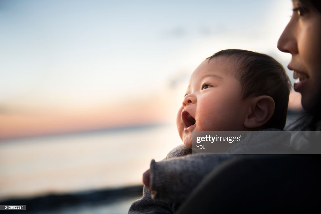 A Baby and Mother in the sunset ocean. : Stock Photo