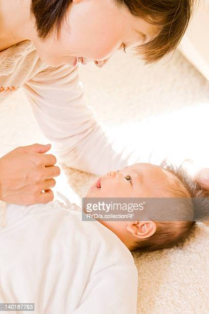 baby and mother looking at each other - 吹田市 ストックフォトと画像