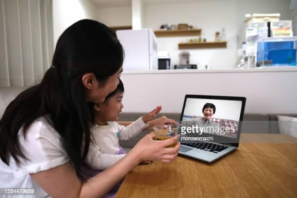 赤ちゃんと母親はビデオ通話で祖母に会う - 人里離れた ストックフォトと画像