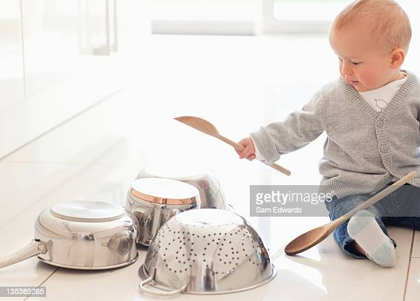 Baby banging on pots with wooden spoon