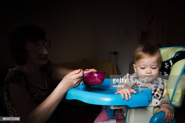 Baby being fed by adult. Picky eater toddler.