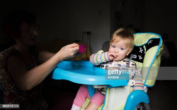 Baby being fed by adult.