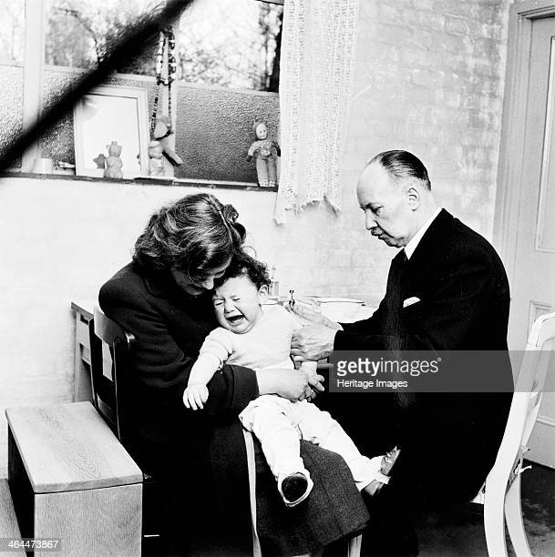 Baby being immunised London 1953 A doctor administers an injection to a crying baby sitting on his mother's lap at the Haverstock clinic