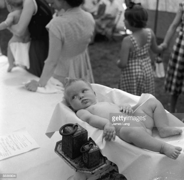 A baby being weighed at a Beautiful Baby contest