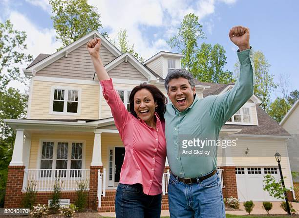 Baby Boomer Couple Celebrating in Front of Home