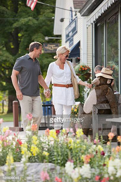 Baby Boomer couple strolls along small town street