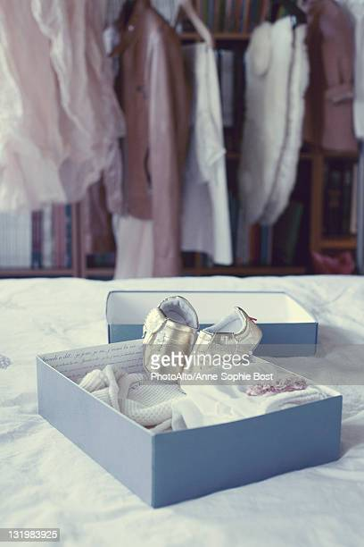 Baby booties and baby clothing in box
