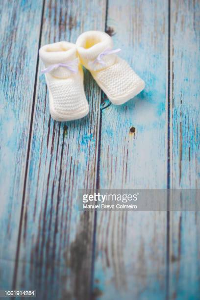 baby booties on a wooden table - baby clothing stock pictures, royalty-free photos & images