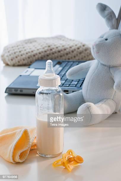 Baby bottle beside laptop