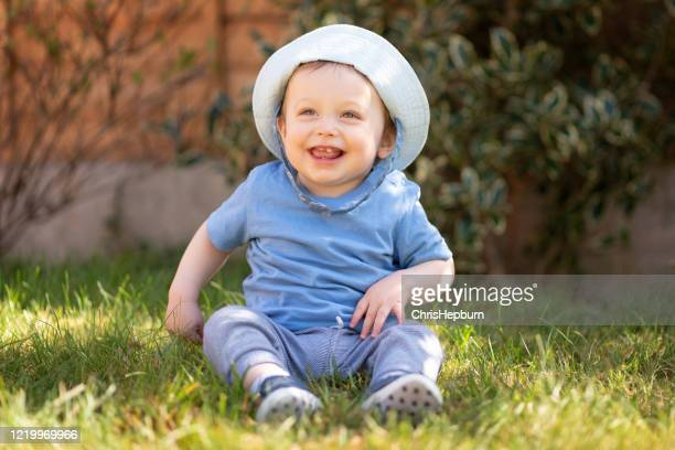 baby boy 10 months old looking away and smiling whilst sitting in the garden - one baby boy only stock pictures, royalty-free photos & images
