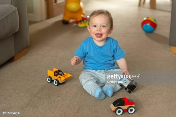 baby boy 10 months old sitting on floor playing with toy cars - one baby boy only stock pictures, royalty-free photos & images