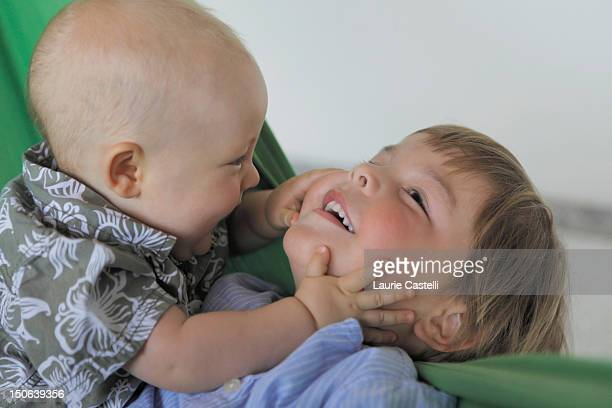 Baby boy and brother playing on couch