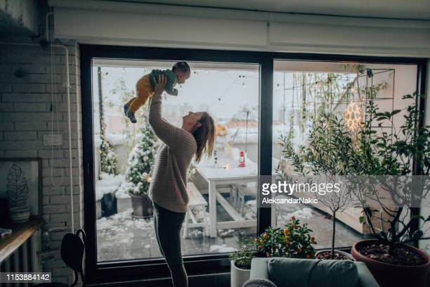 baby boy and his mom in their apartment - winter house stock pictures, royalty-free photos & images