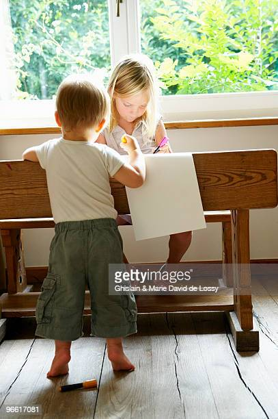 Baby boy and his sister drawing