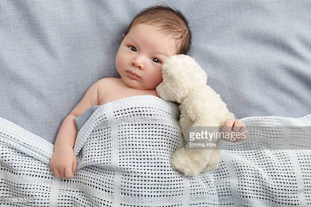 Baby boy and teddy bear laying in bed