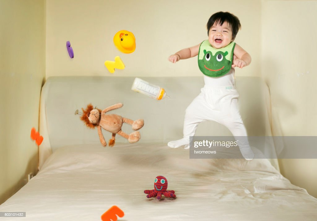 Baby boy and toys jumping on bed. : Stock Photo