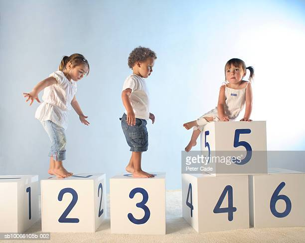 Baby boy (21-24 Months) and two girls (2-5) climbing on lettered white boxes