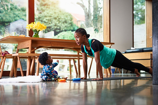 Baby boy assisting mother exercising - gettyimageskorea
