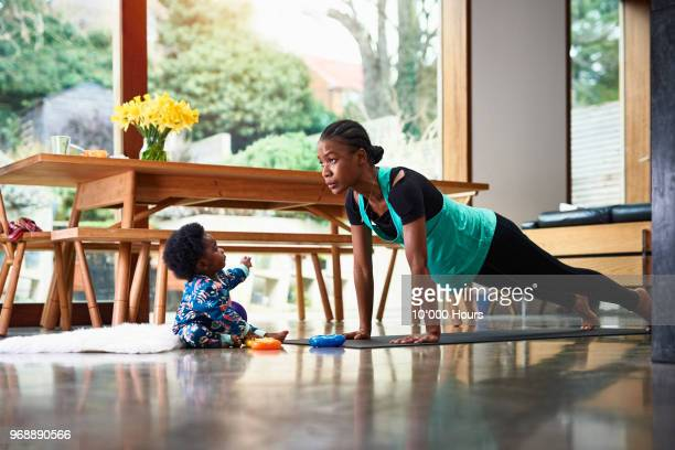 baby boy assisting mother exercising - exercising stock pictures, royalty-free photos & images