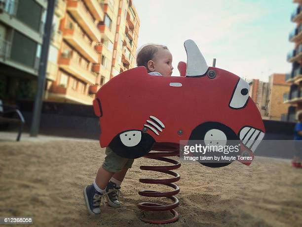 baby boy behind wood car at the playground - chert stock photos and pictures