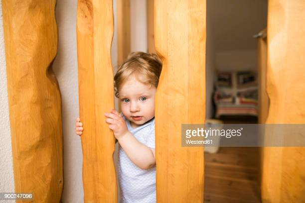 baby boy behind wooden barrier - parapetto barriera foto e immagini stock
