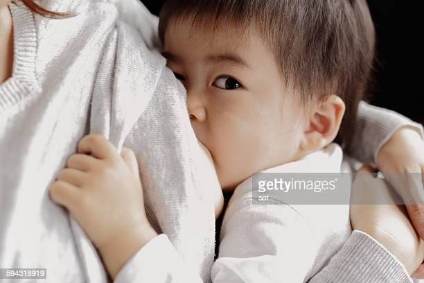 baby boy being breastfeeding fed,close up - japanese breastfeeding stock pictures, royalty-free photos & images