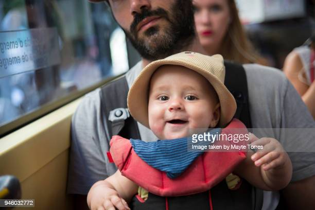 Baby boy being carried by dad at the bus
