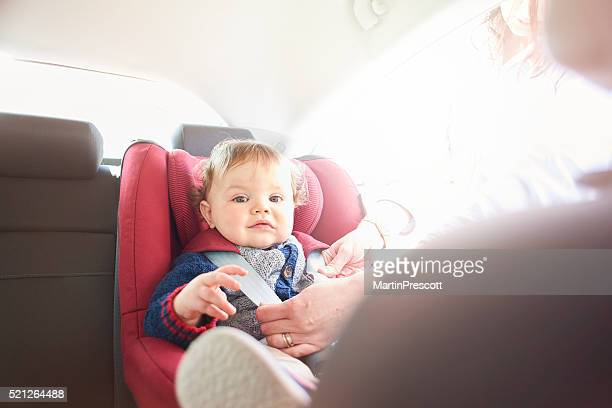 Baby boy being fastened in car seat