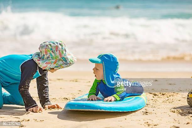 Petit garçon être appris à surfer grâce à son frère