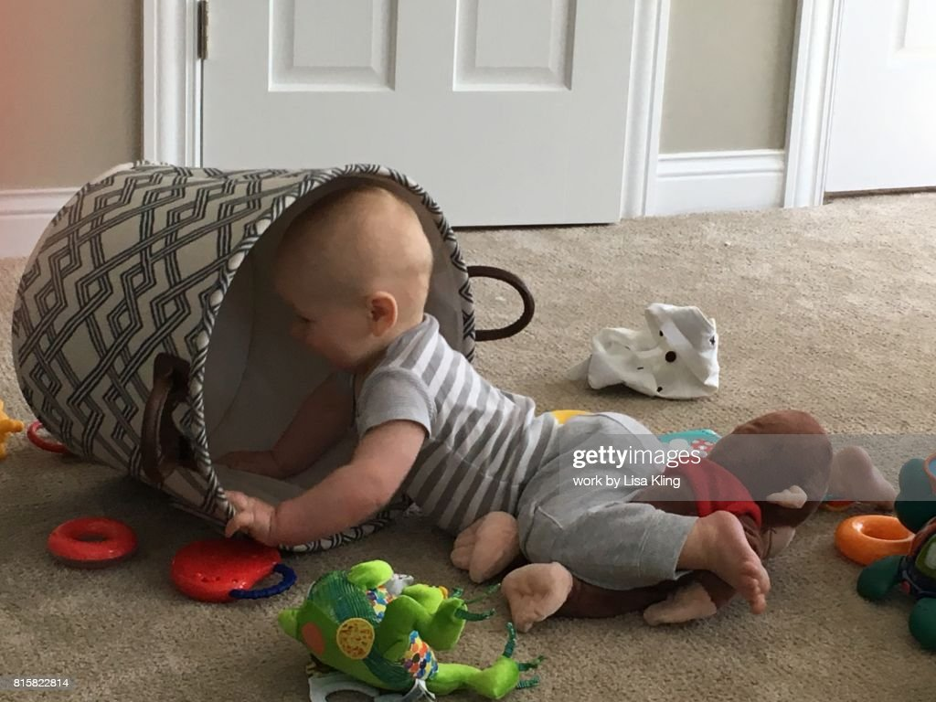 Baby boy busy playing with toys in a basket : Stock Photo